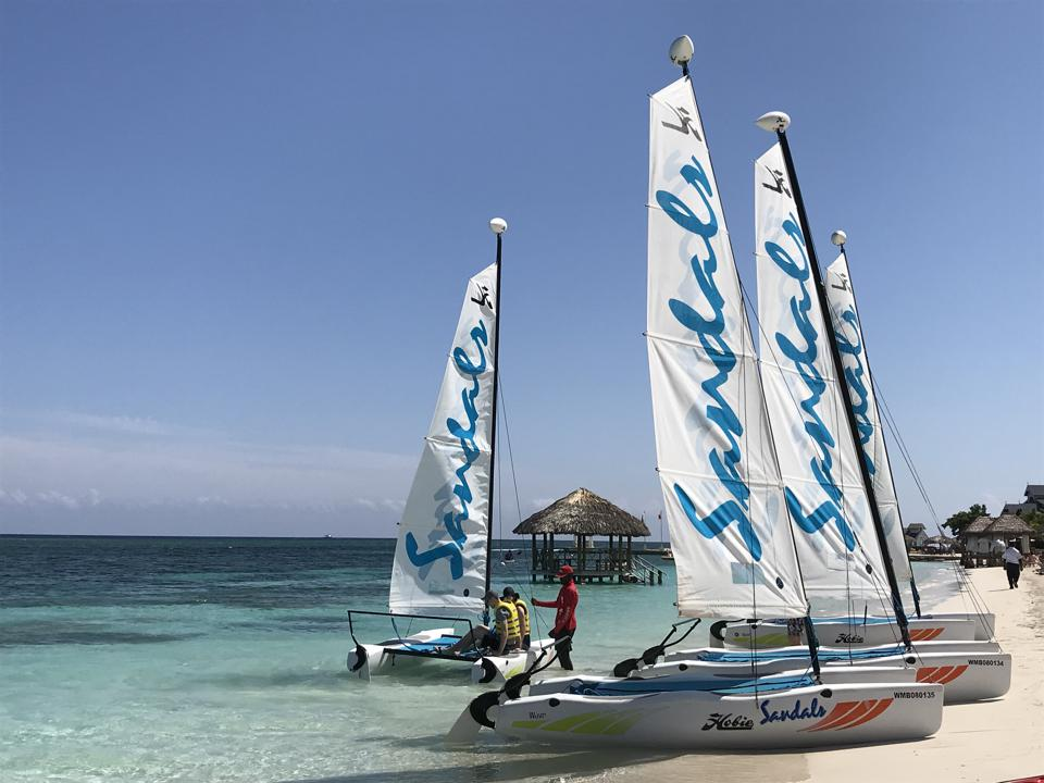 Several catamarans with ″ Sandals ″ written on the sails;  one has two people on it with a staff member standing in the shallow water to help them get started.