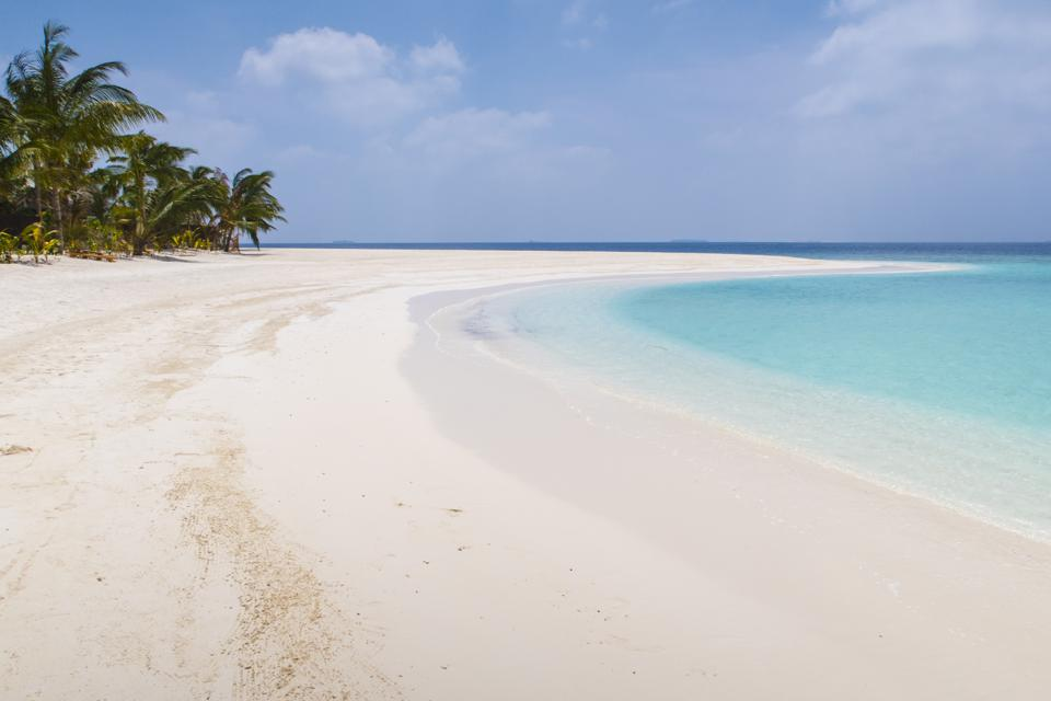 A wide, white sand beach with palm trees curves next to clear blue water.