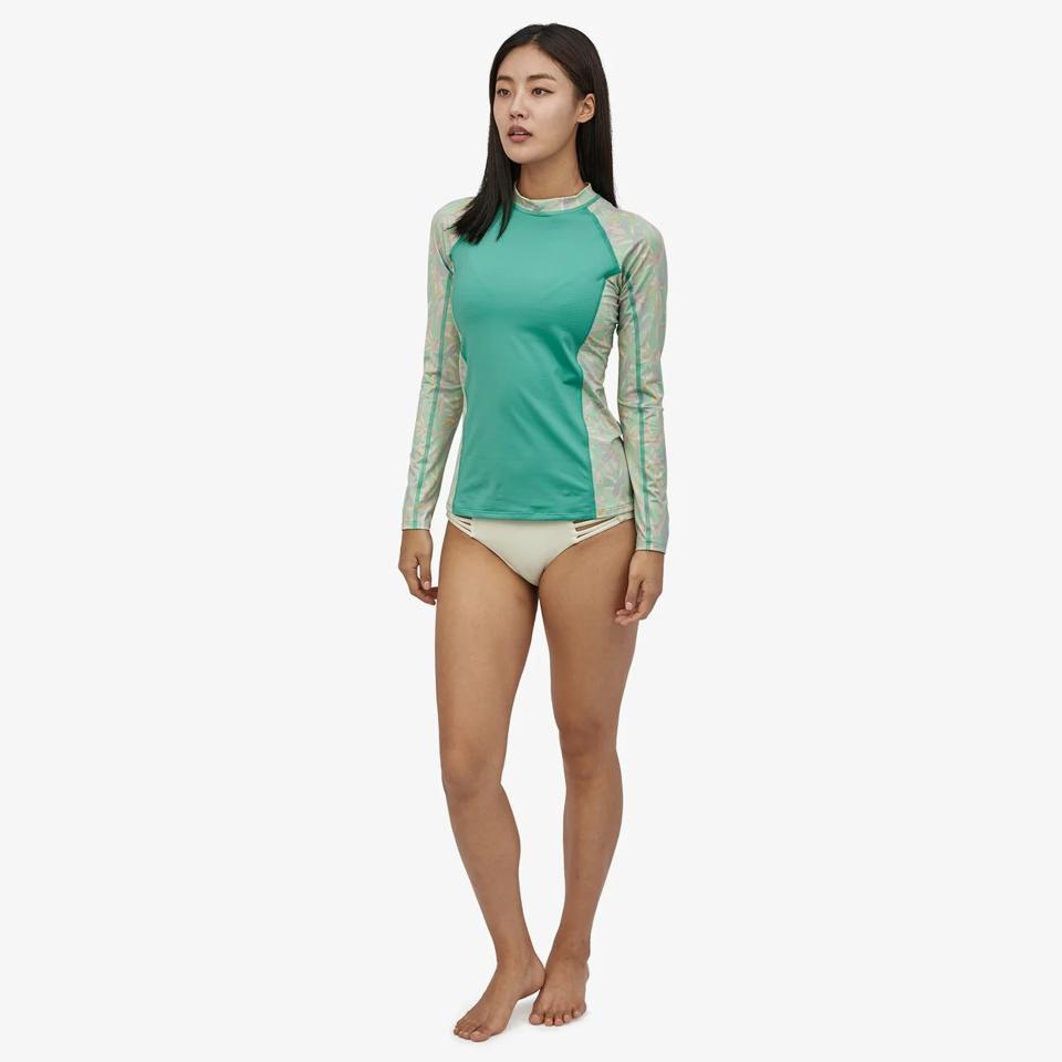 Model in white Patagonia white bikini bottoms an green rash guard.