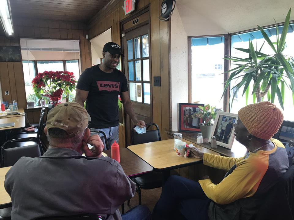 A Black man standing and talking to an older White man and Older Black woman sitting at a table in a restaurant.