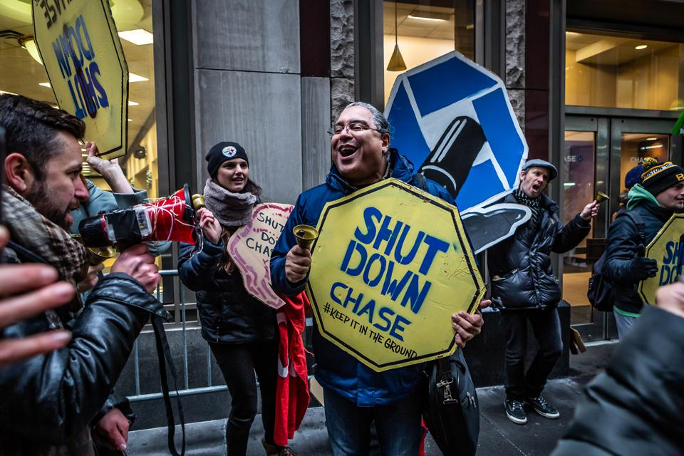 A protester marches through Wall Street chanting ″Stop...