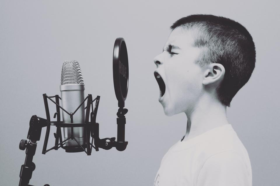 Photo of a young boy yelling into a microphone.