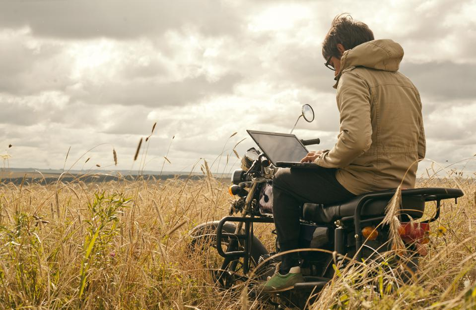 Mari man using laptop on motorcycle in rural field