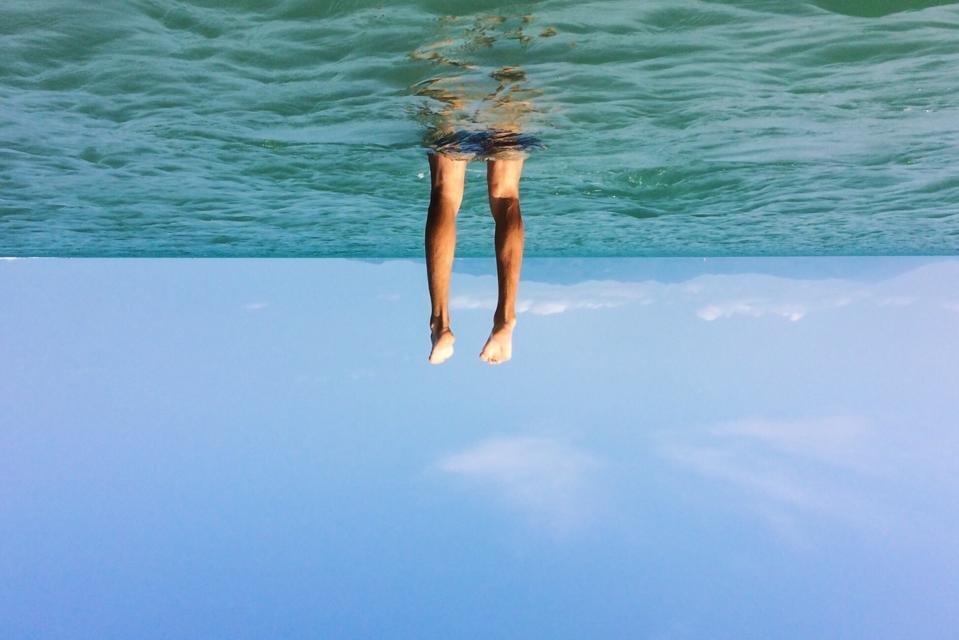 Tilt Image Of Man Swimming In Sea Against Sky