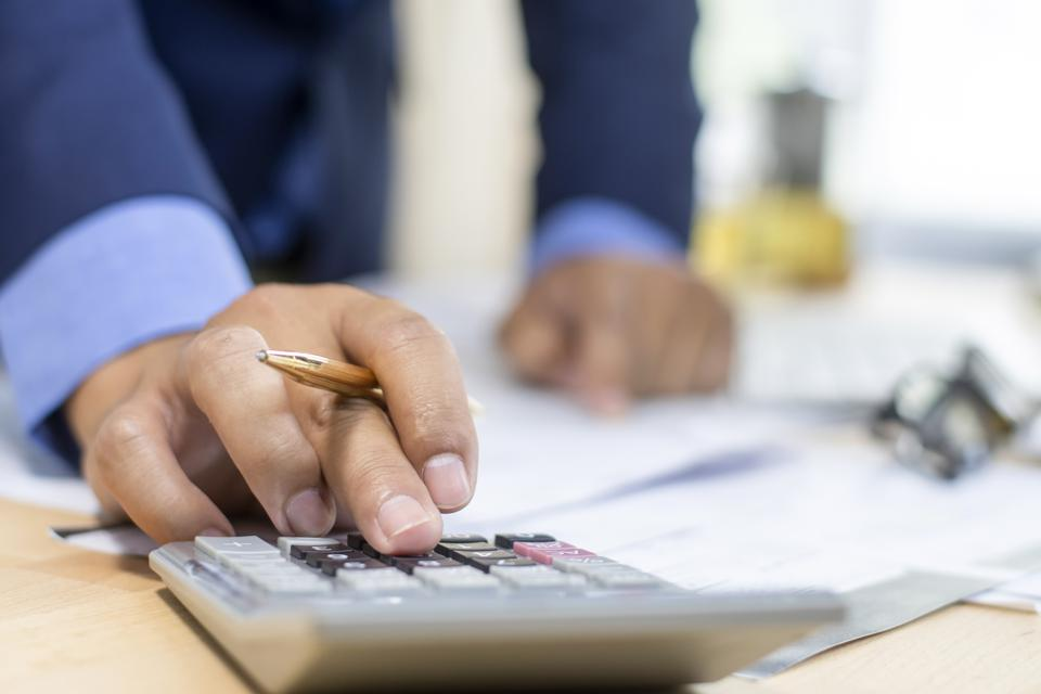Close up Businessman using pen and calculator working on wooden desk