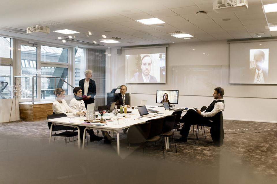 Mature businesswoman planning strategy with team in board room during web conference meeting at office