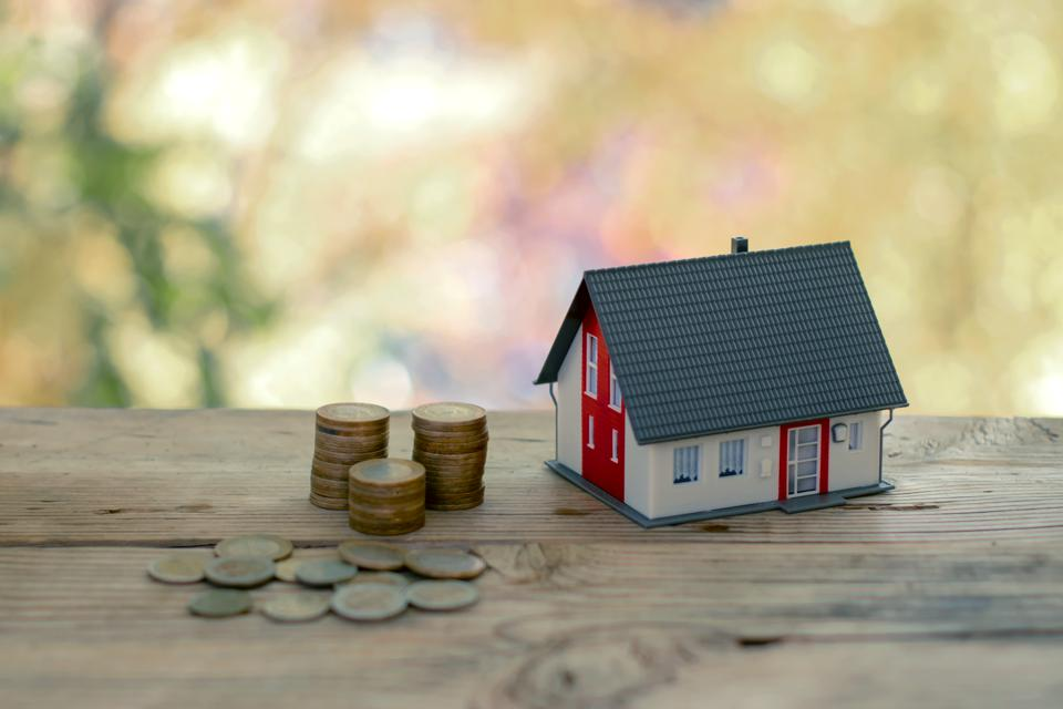 Real Estate Investment. House and coins on wooden table