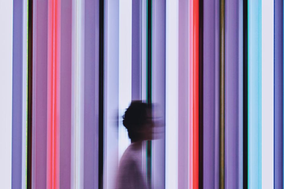 Blurred Image Of Woman Walking Against Illuminated Lights At Art Gallery