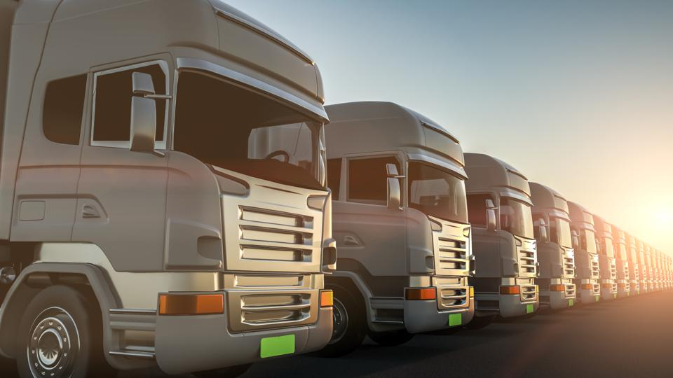 Row of cargo electric trucks against with sun