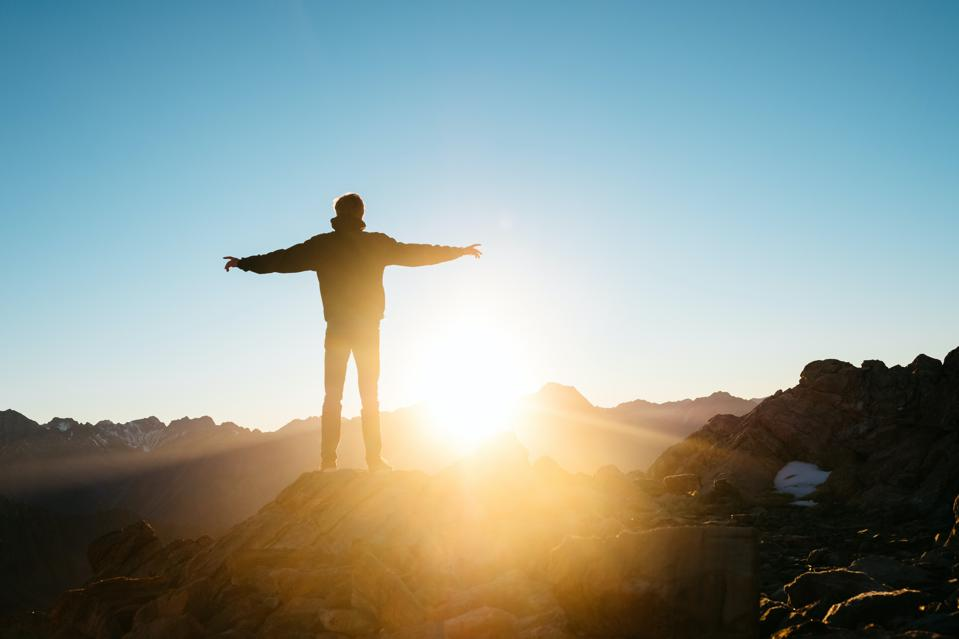 Man standing on top of a mountain during sunrise with arms stretched to the side.