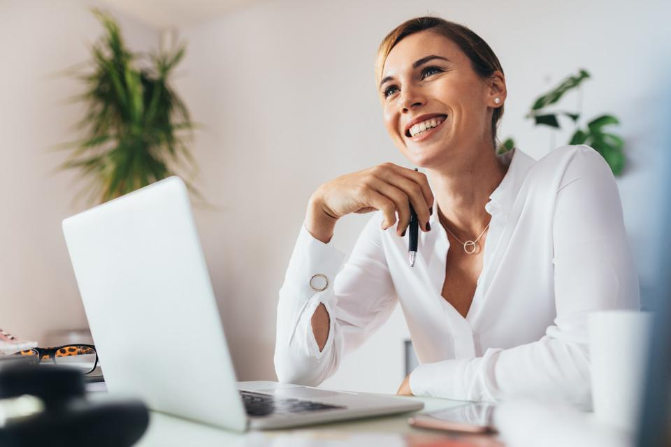 Business woman wearing a white dress shirt while working on her lap top.