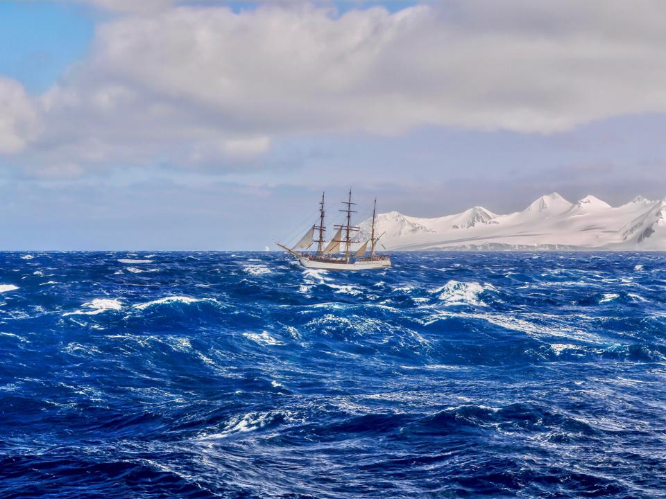 A traditional tall ship with reefed sails sailing through rough seas in the southern pacific ocean.
