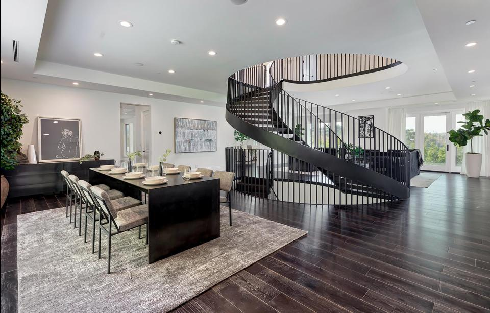 A dining room and spiral staircase.