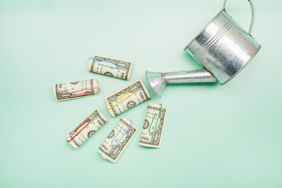 Watering can and American Dollar banknotes on turquoise background