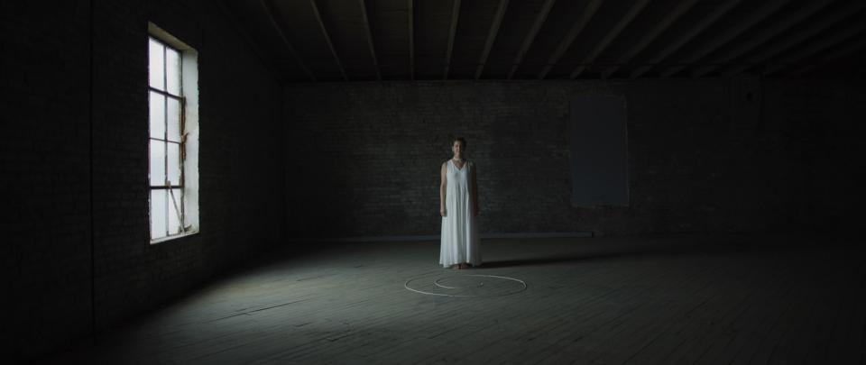 A woman in a white dress stands in a dark room, lit by a single window.