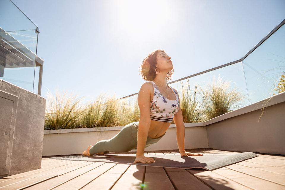a young woman in an upward facing dog yoga position on a deck during the day