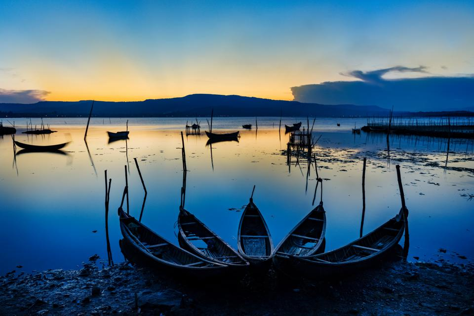 canoes on a glassy lake at sunset