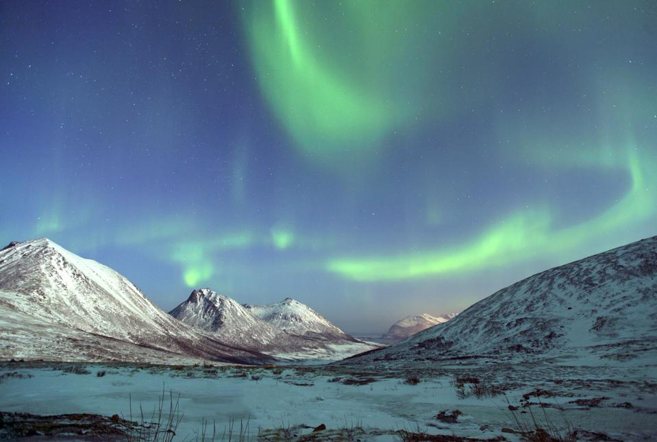 The Northern Lights over snowy mountains