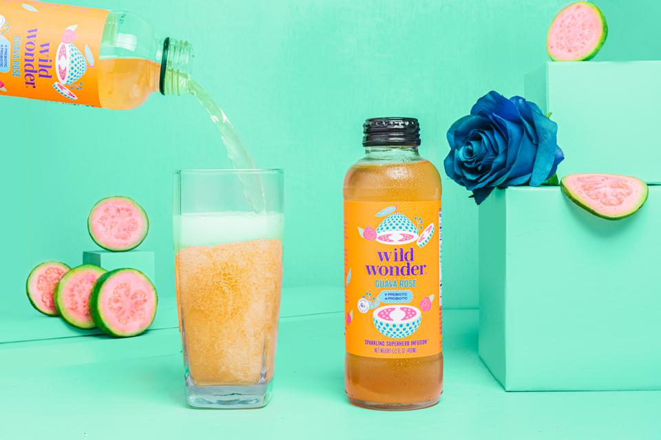 A bottle of Wild Wonder Guava Rose flavor next to a full glass of the drink.