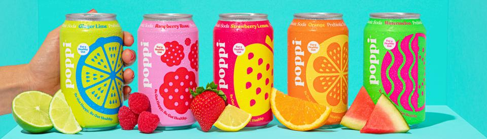 Five bright cans of Poppi soda against a teal backdrop and decorated with real fruit.