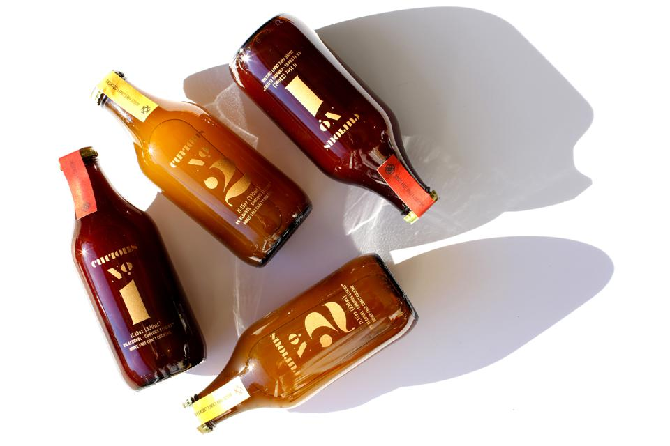 A flat-lay of four bottles of Curious Elixirs on a white table.