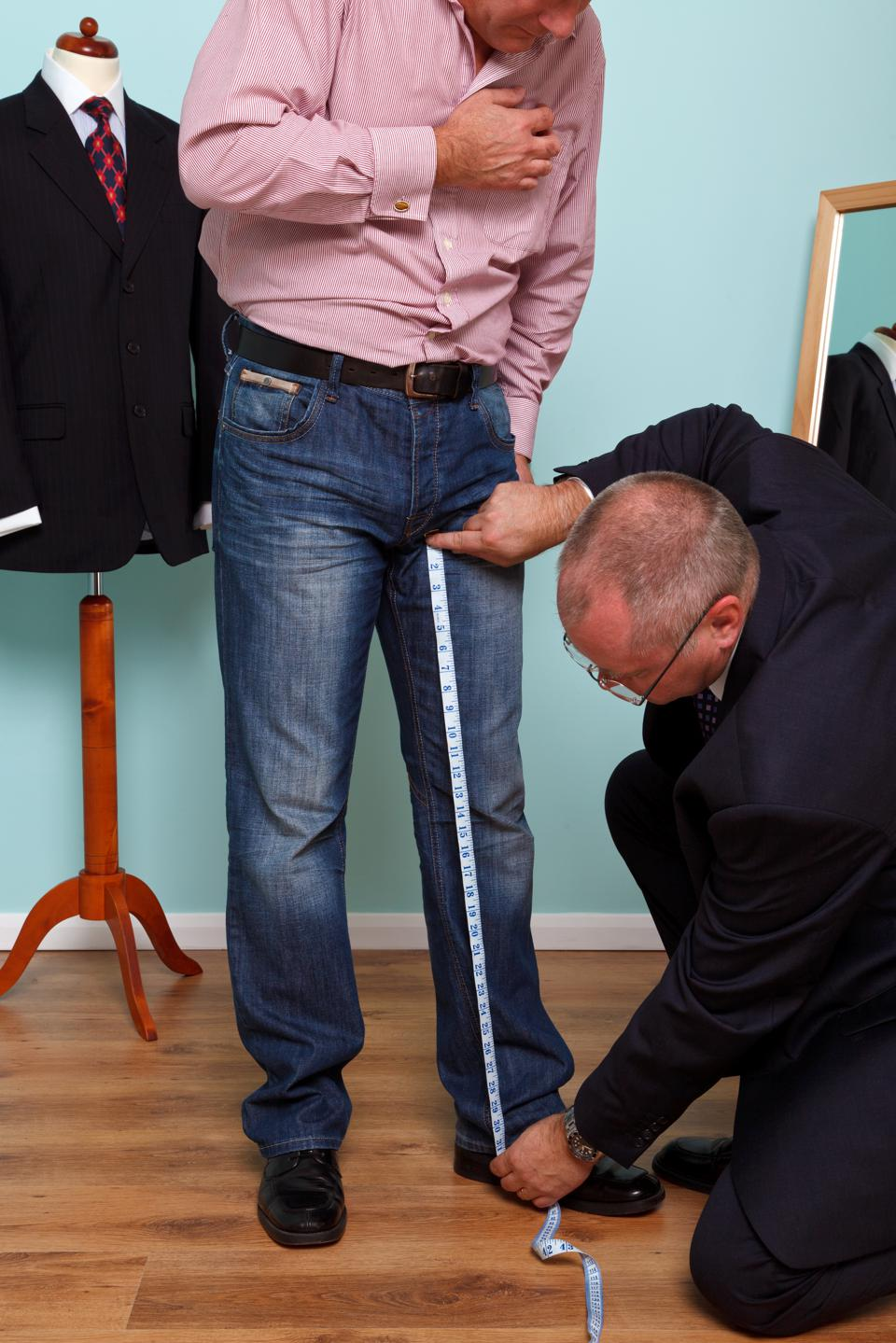 Inside leg being measured by a tailor during suit fitting