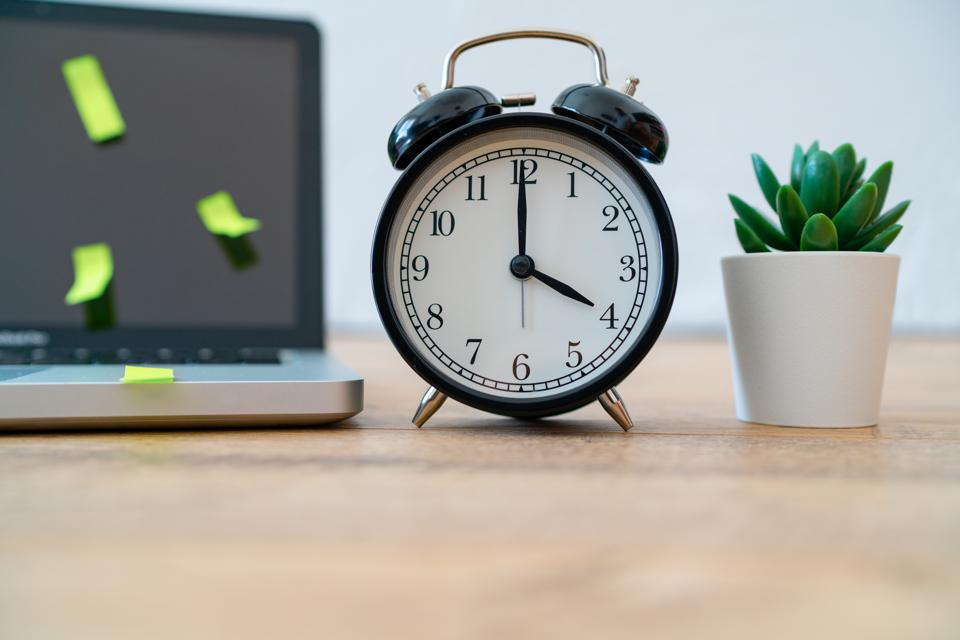 Alarm clock, laptop with postit notes and plant showing work-from-home productivity isn't what you thought.
