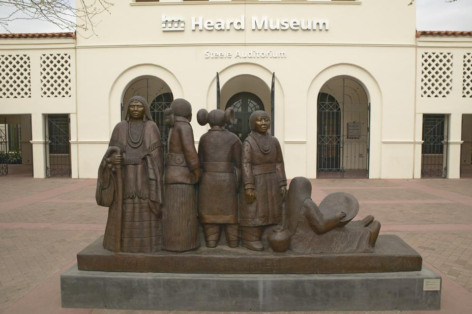 The front entrance of the Heard Museum showing a sculpture of Native Americans in Phoenix, Arizona