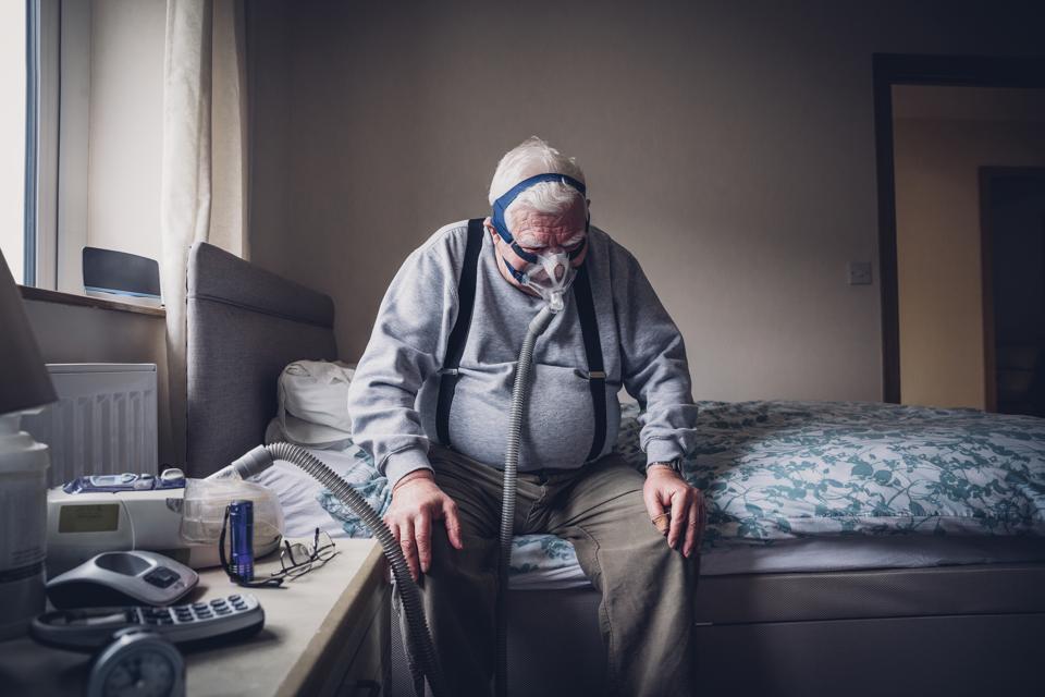 Elderly Man Using a Medical Breathing Apparatus