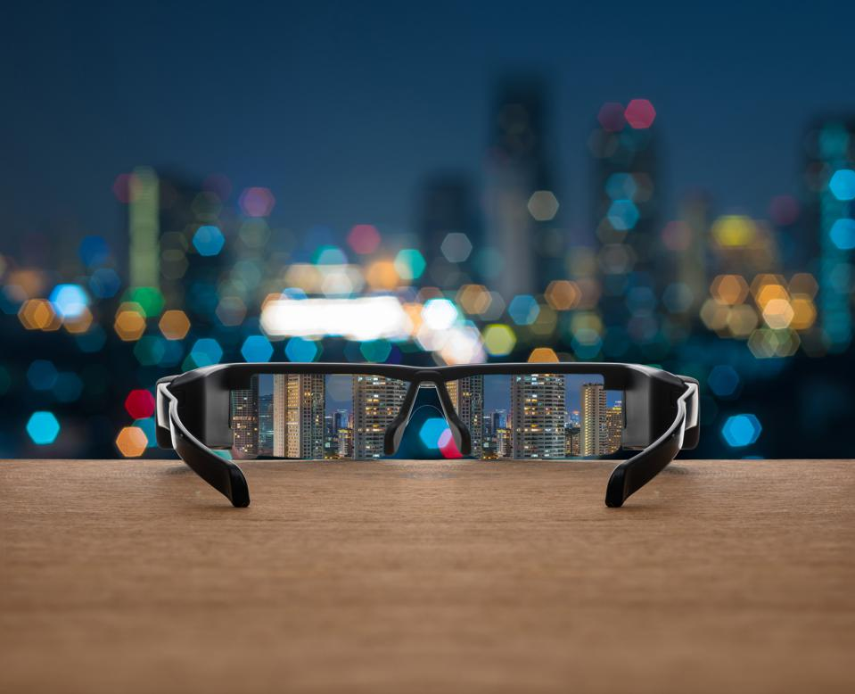 Cityscape focused in glasses lenses on the wooden over the abstract photo blurred of cityscape background, business success concept.