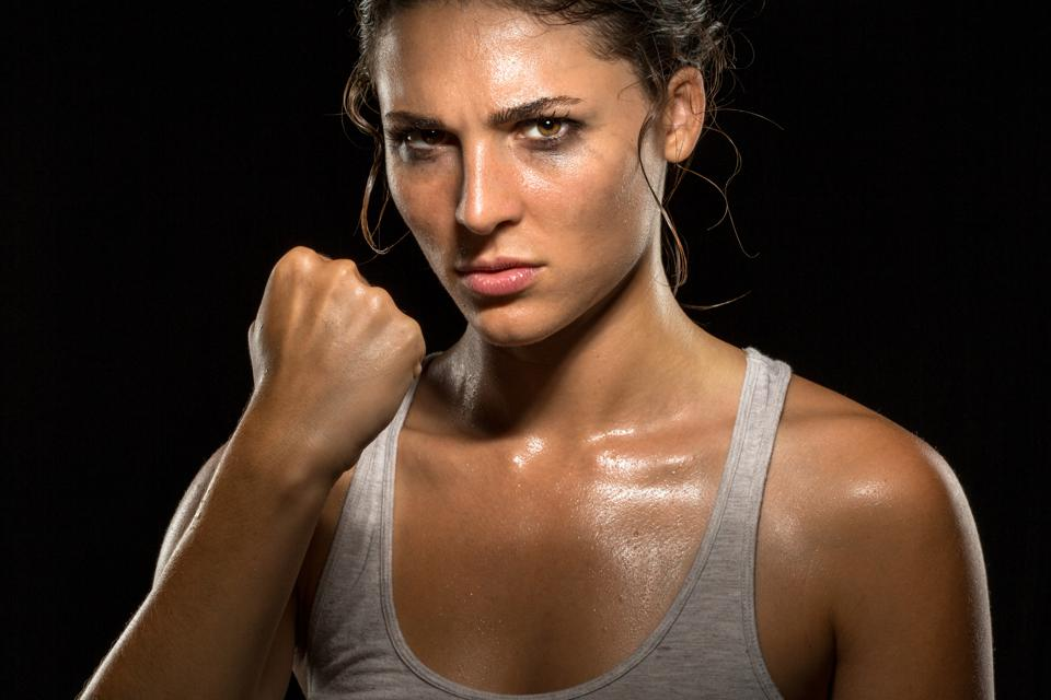 tough woman athlete exercising and making a fist