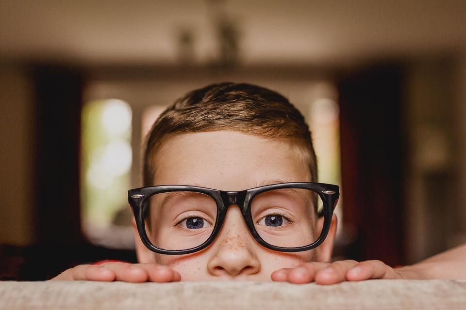 Portrait of peeking boy wearing oversized glasses