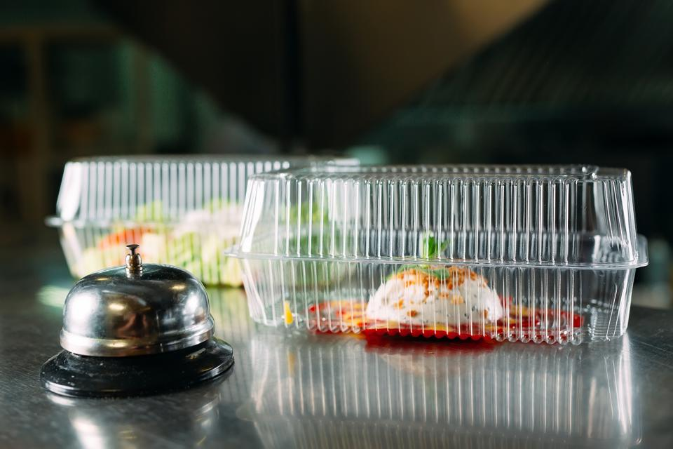 food delivery. distribution table in a restaurant with a metal bell. food in plastic containers. Panna cotta and vegetable salad in a plastic disposable containers.