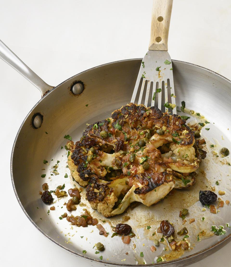 A sautéed cauliflower steak with a lemon, anchovy, caper sauce is photographed in a stainless-steel sauce pan with a stainless spatula lifting it up. The photograph is from ″Flavorbomb″ cookbook by Bob Blumer.