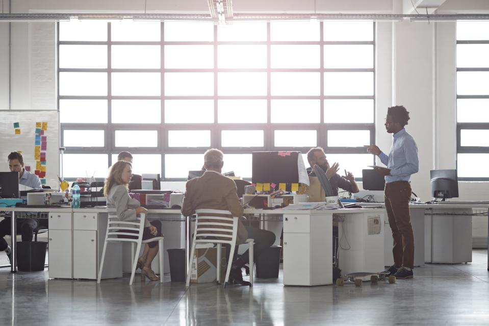 Employees working at an office with an open floor plan.