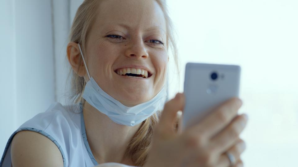 A young woman in a mask during the quarantine period communicates in the video chat.