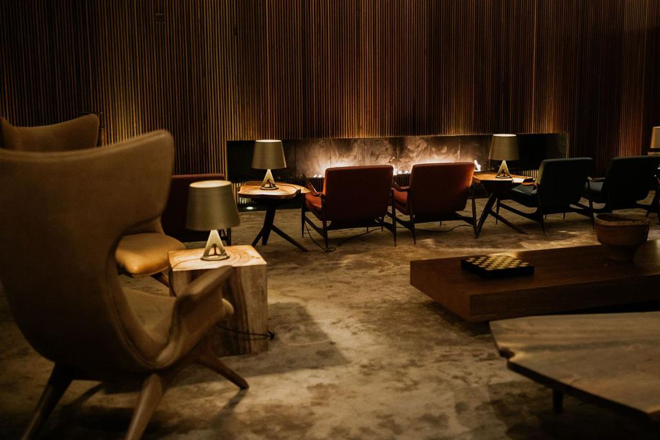 Chairs sit on front of a long, modern fireplace at L'AND Vineyards hotel in Portugal