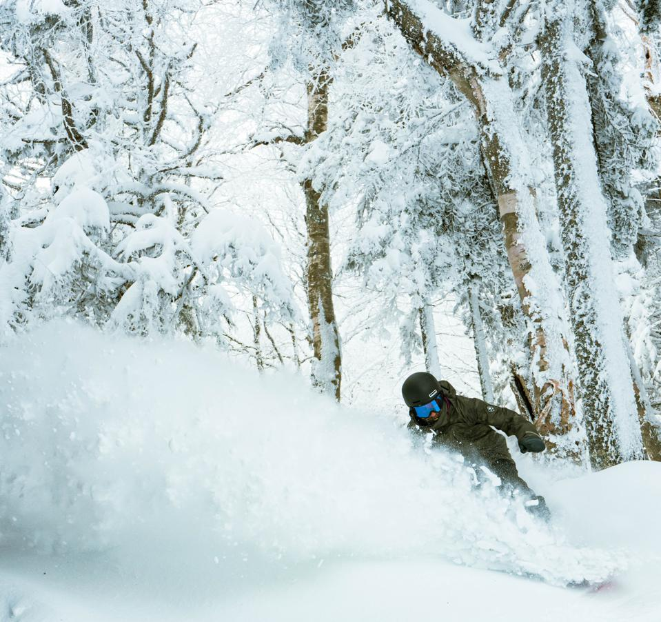 A snowboarder riding the powder at Stratton Mountain Resort.