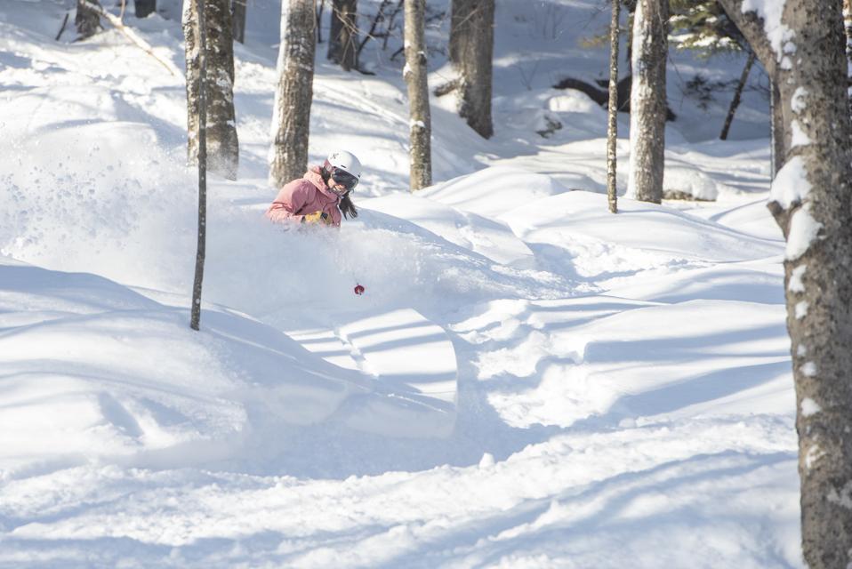 A skier coming through powder at Sunday River.