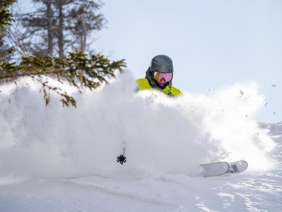 A lone skier kicking up powder at Waterville Valley.