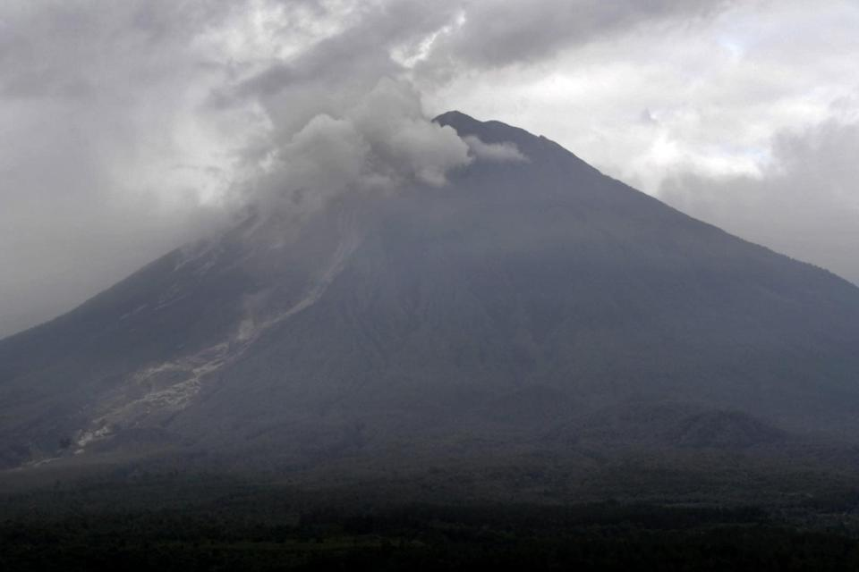 Mount Semeru with a plume of volcanic material hovering above its crater and path of a pyroclastic flow along its slope.