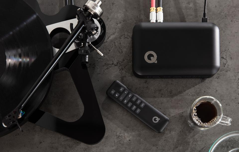 Q Active hub and remote next to a turntable