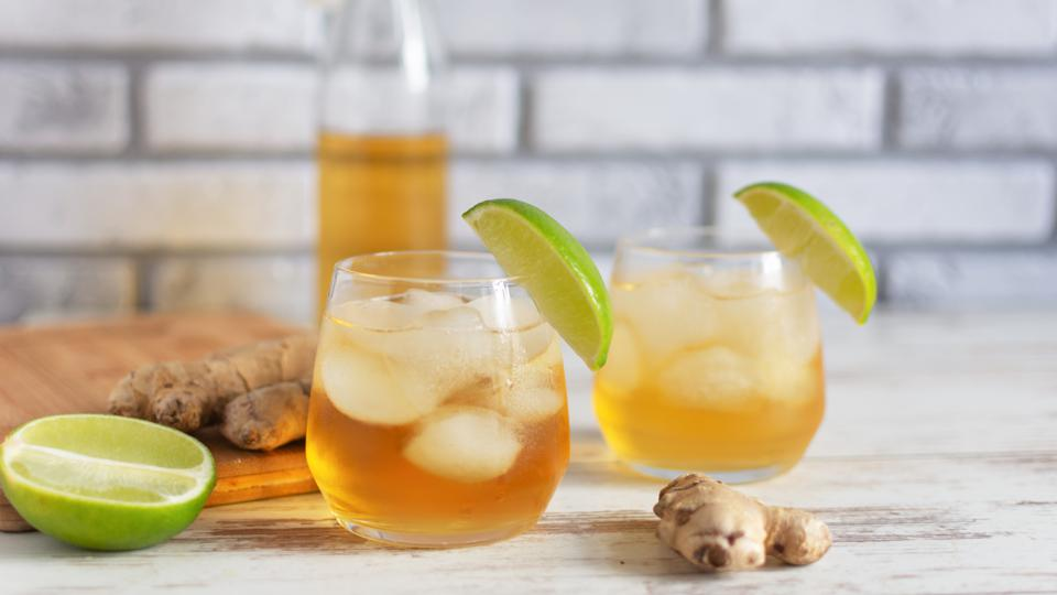 Fresh Ginger Ale with lime and ice or Kombucha in Bottle - Homemade lemon and ginger organic probiotic drink.