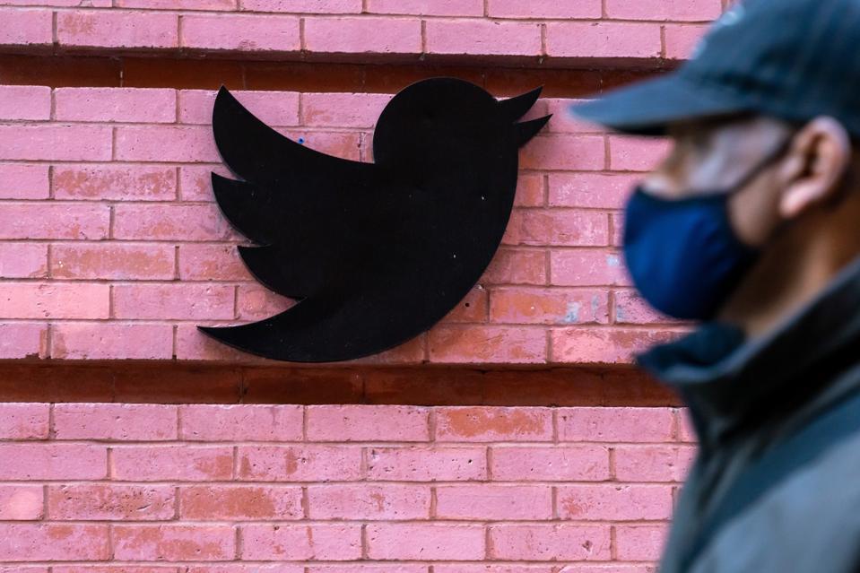 A man wearing a face mask walks past a Twitter logo outside...