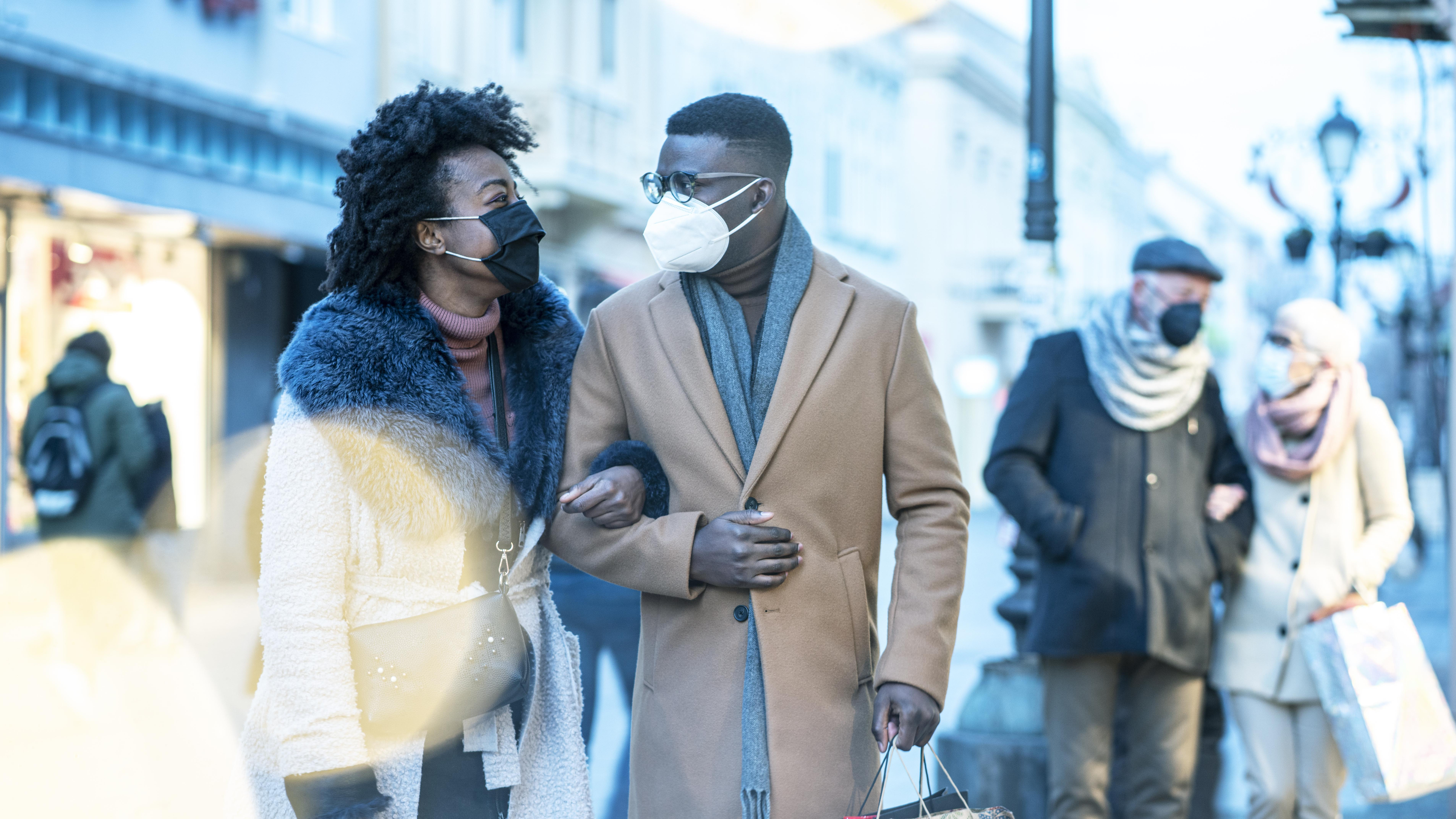Young couple at Christmas shopping, COVID-19 pandemic. They wearing a protective mask to protect from corona virus COVID-19