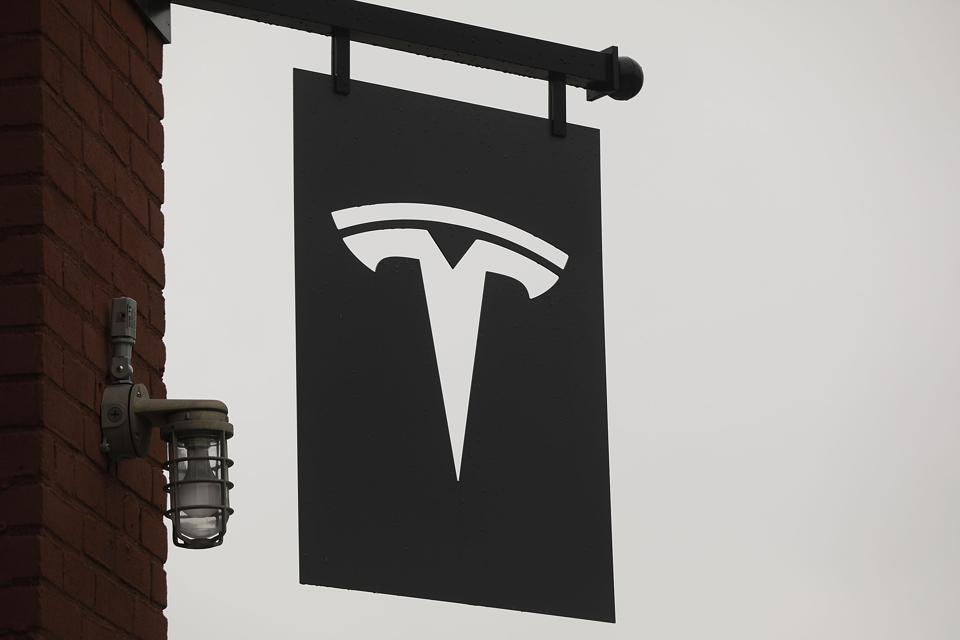 Tesla logo hanging from banner outside a building