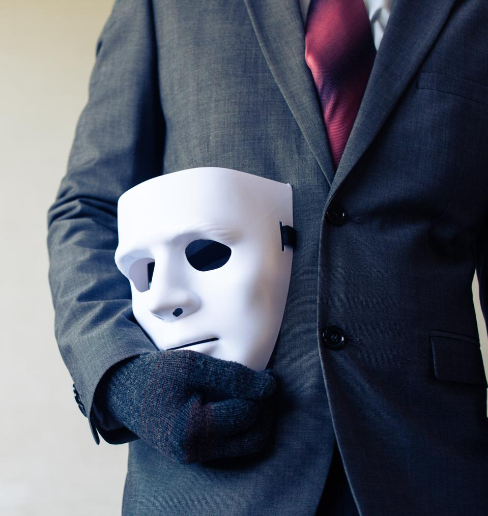 Businessman carrying white mask - business fraud and faking concept