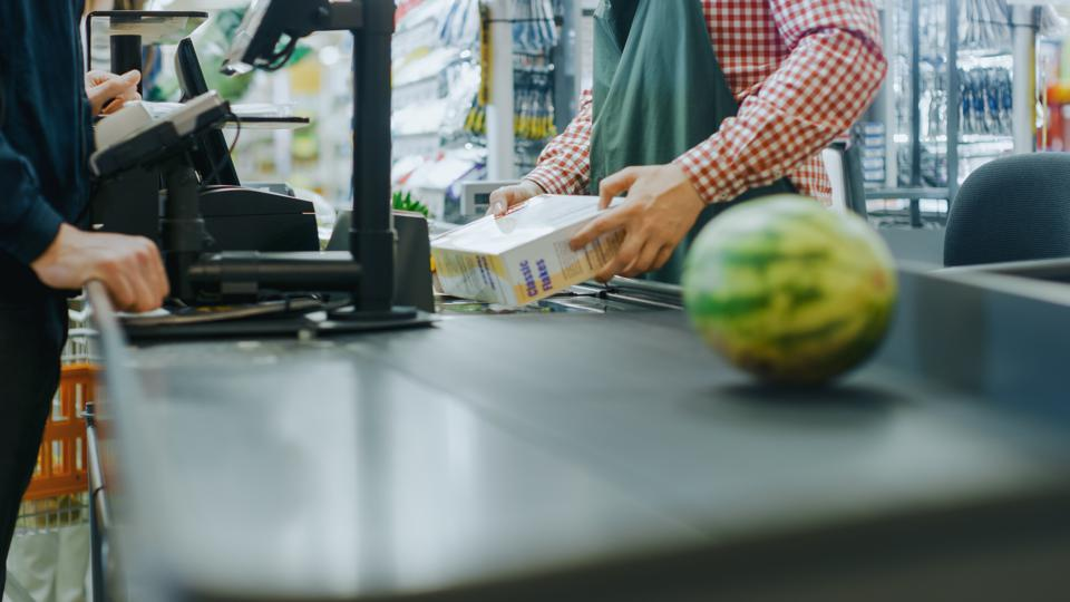 At the Supermarket: Checkout Counter Hands of the Cashier Scans Groceries, Fruits and other Healthy Food Items. Clean Modern Shopping Mall with Friendly Staff, Small Lines and Happy Customers.