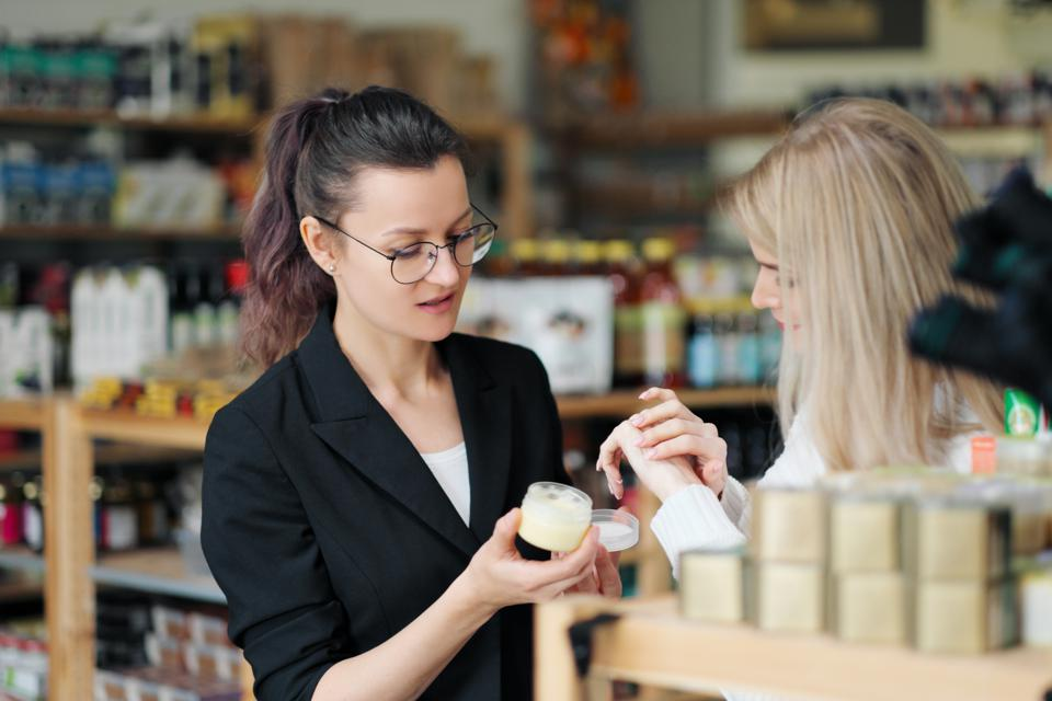 A young attractive blonde woman in a white sweater shopper in the store chooses cream. Cosmetics and beauty store.