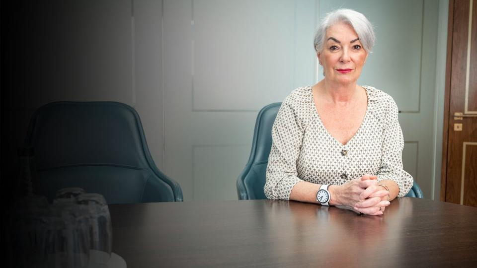 Avril Millar sitting at a boardroom table.
